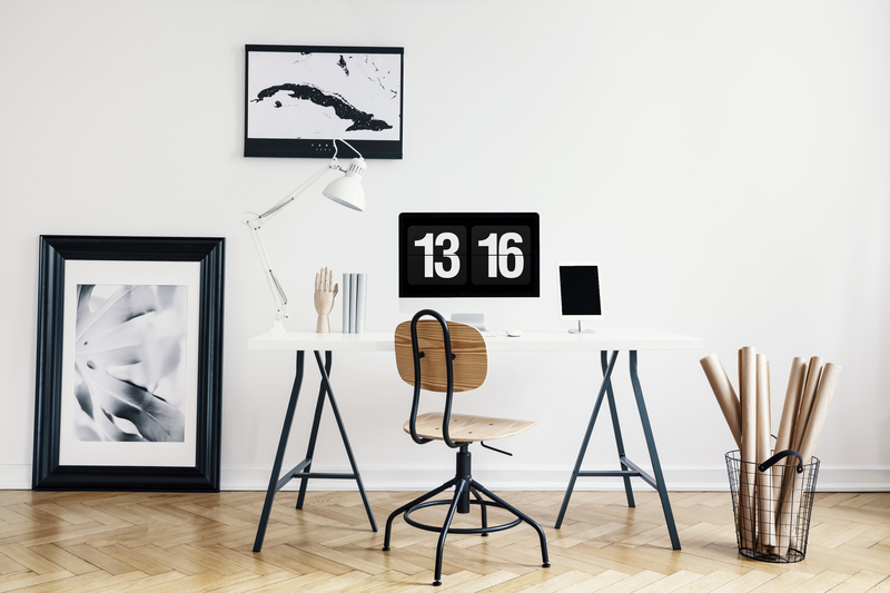 Industrial basket with kraft paper rolls and a framed poster in a white, minimalist home office interior of a freelancer architect. Real photo.